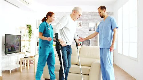 Two Nurses Helping an Old Disabled Man with Crutches To Walk in His Room