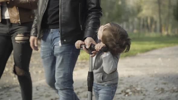 Fröhlicher süßer kaukasischer Junge, der mit unkenntlichen Eltern Roller im sonnigen Park reitet