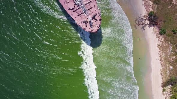 Cover Image for Drone Flies Over Green Sea Washing Cargo Vessel Moored To Beach