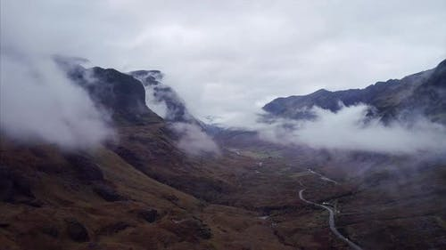 Aerial Panning Shot of Fog Clouds Over The Three Sisters of Glencoe