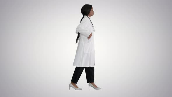 Thumbnail for Sad African American Female Doctor Walking with Hands in Her Pockets on Gradient Background