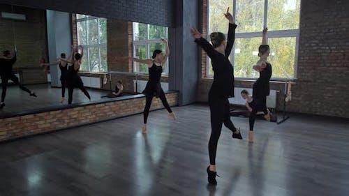 Slim Dancers Training Grand Jete in Ballroom