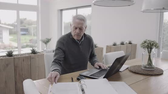 Senior adult male doing domestic finance on laptop at home on table, day in life