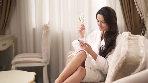 Thumbnail for A Pretty Brunette in a White Gown Sits on the Couch, Holding a Phone