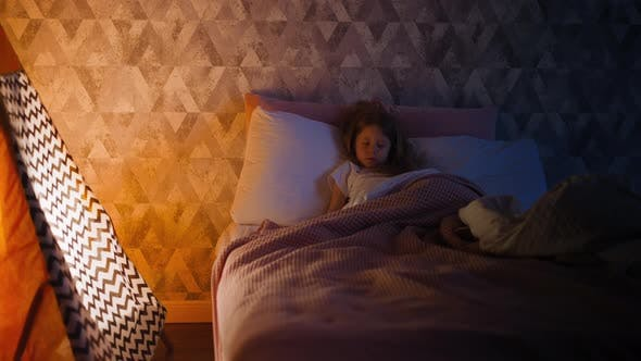 Little Girl Sleeps Tight on Bed By Children Teepee at Home