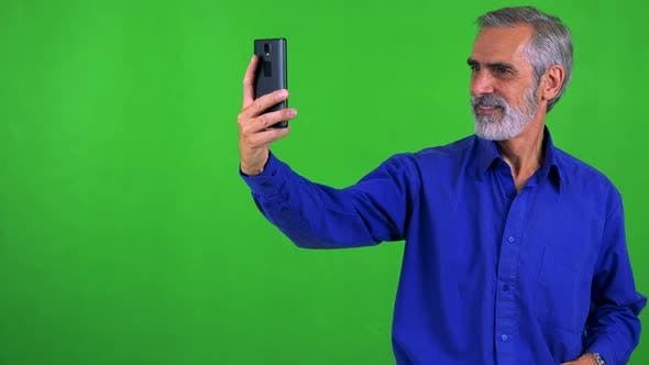 Thumbnail for Old Senior Man Photographs with Smartphone (Selfie) - Green Screen - Studio