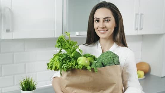 Woman Holding Bag with Green Vegetables