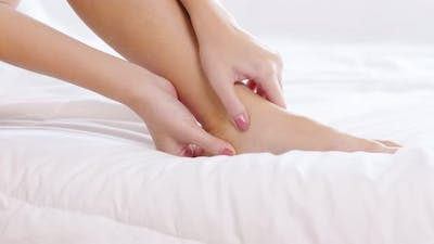 young Asian woman have a ankle pain massage on pain spot