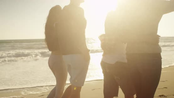 Thumbnail for Couples walking on the beach together during sunset