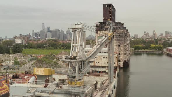 Thumbnail for Over Old Rusty Cargo Ship Crane and Warehouse with New York City Skyline in Background on a