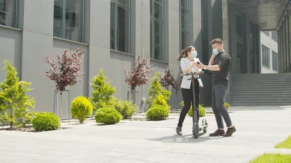 Thumbnail for Young Man and Woman Businesspeople Talking and Smiling with Smartphone in Hands on the Street in