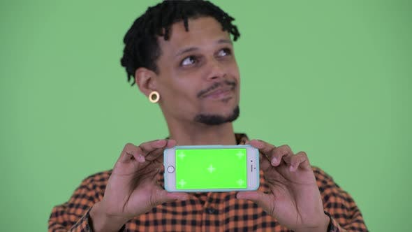 Thumbnail for Face of Happy Young Handsome African Man Thinking While Showing Phone