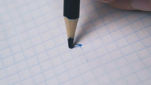 Person Draws and Breaks Pencil Slate on Paper Macro