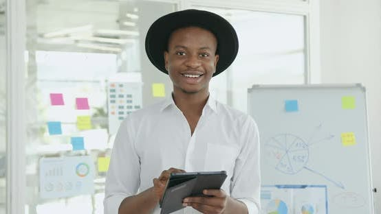Thumbnail for African American in Black Hat and White Shirt Looking Into Camera in Contemporary Glass Office