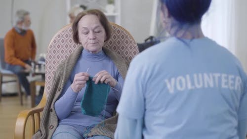 Portrait of Positive Mature Caucasian Woman Talking with Unrecognizable Volunteer in Nursing Home
