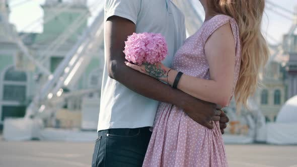 Young Interracial Couple Hugging Near Ferris Wheel in the City
