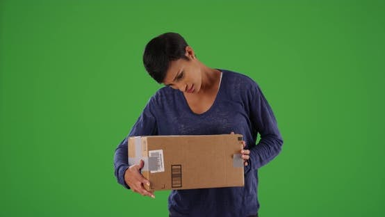 Thumbnail for Female shaking cardboard box excitedly, guessing what's inside on green screen