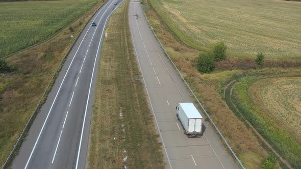 Thumbnail for Aerial View of Truck with Cargo Trailer Driving on Straight Road and Transporting Goods. Camera