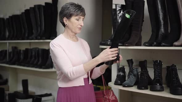 Thumbnail for Senior Elegant Woman Examining Winter Boot in Shoe Store and Calling for Salesman. Portrait of