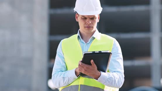 Professional Architecture Inspector Working with Digital Tablet at Construction Site, Tracking Shot