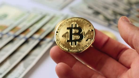 Hand showing gold bitcoin cryptocurrency.