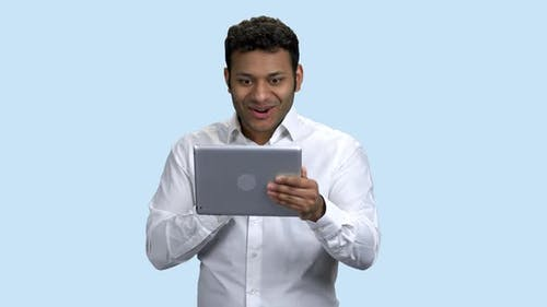 Shocked Man Looking at Digital Tablet