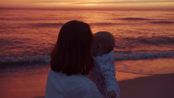 Mom and baby on the background of the sea sunset