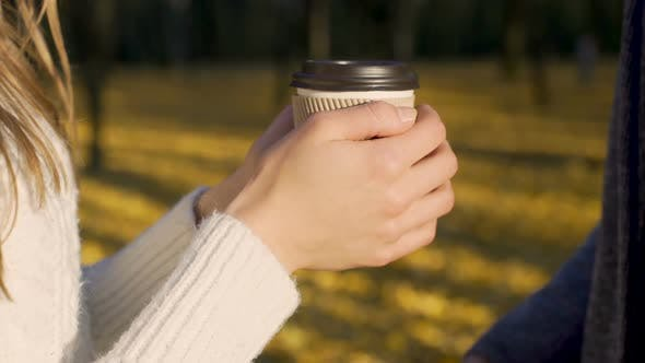 Thumbnail for Lovers warming their frozen hands with cup of warm beverage, autumn date