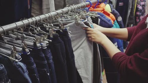 Woman Hand Chooses a Pants for the Boy in the Second Hand Shop