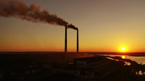 Smokestack in factory with yellow cloudless sky