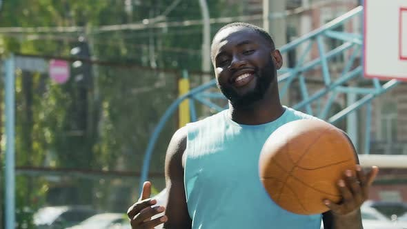Thumbnail for Happy man throwing ball from one hand to another, proud of streetball victory