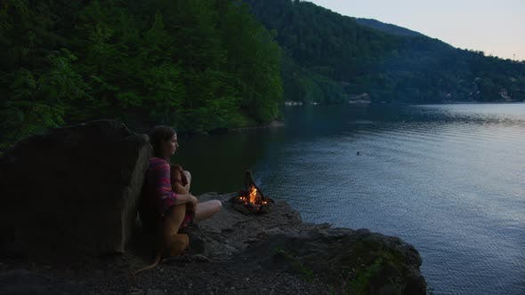 Thumbnail for Girl and dog at a campfire near a lake