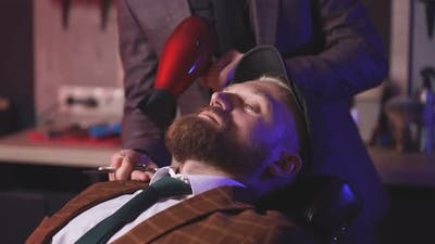 Stylish Man Sits in a Barbershop While a Barber Dries His Beard