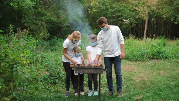 Dad, mom and children fry meat on skewers on the grill. Family in medical masks at a picnic