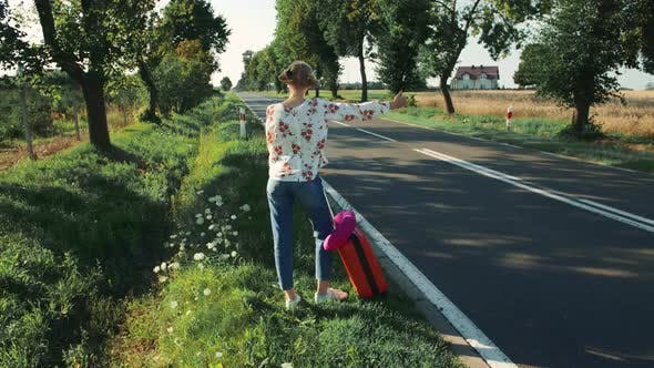 Thumbnail for Young Woman Hitchhiking on Countryside Road.