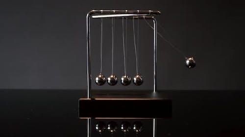 Hand Pulling Ball of Newton Cradle