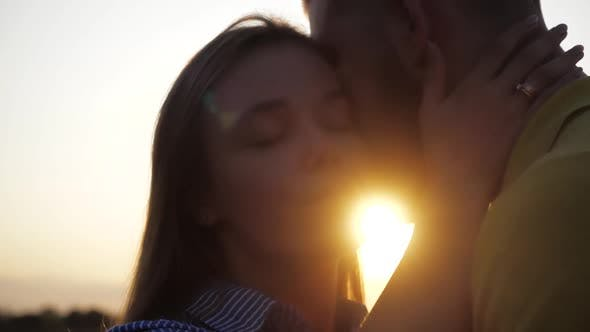 Thumbnail for Close-up Shooting of Loving Cute Couple Kiss on a Romantic Date Against the Sunset. Close View of