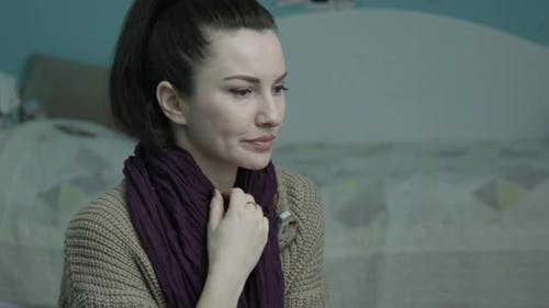 Woman Is Coughing Wrapped In A Scarf And Checking Temperature With A Thermometer