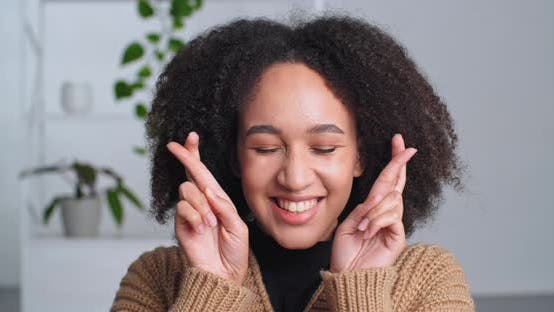 Sincere African American Girl with Afro Curls Hairstyle Smiling Crossing Fingers Making Gesture of