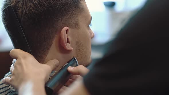 Young Man Sits in a Barber Shop He Is Made Up with a Beard Closeup Slow Motion