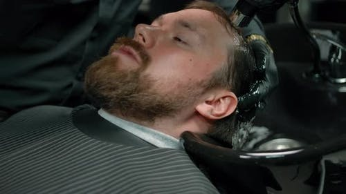 The Head of a Bearded Man is Washed with Shampoo Foam in a Barbershop