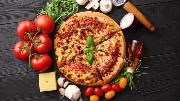 Thumbnail for Delicious Italian Pizza Served on Black Wooden Table