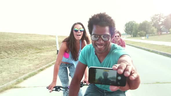 Thumbnail for Three young adults having fun cycling and taking selfies, graded