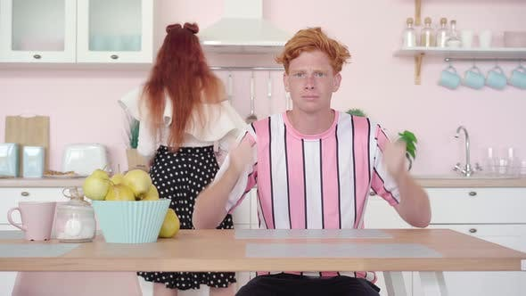 Portrait of Hungry Redhead Man Sitting at the Table in Kitchen Gesturing As Woman Cooking