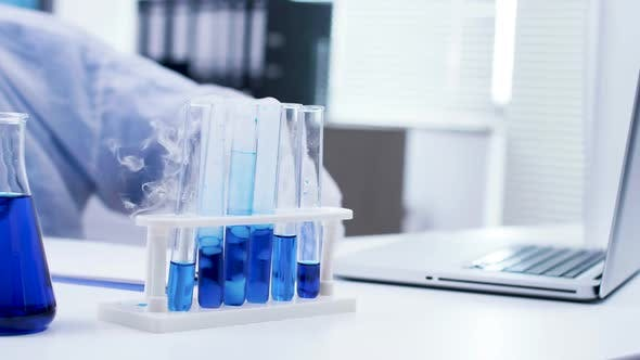 Cover Image for Close Up of Blue Fluid in Test Tubes Making Smoke