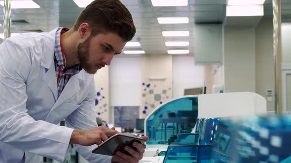 Thumbnail for Man Checks the Work of Lab Device with Tablet