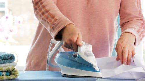 Weibliche Hände bügeln Kleidung mit Bügeleisen auf Bügelbrett