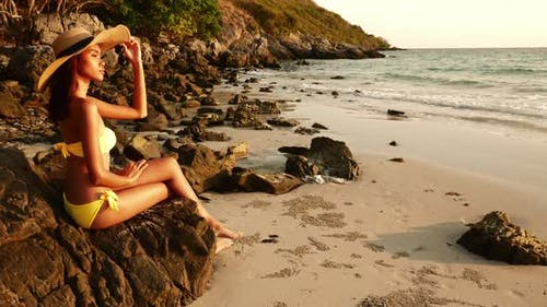 Attractive young woman in bikini sitting on the beach at sunset