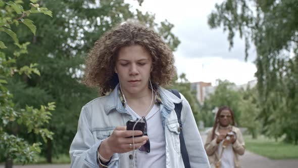 Thumbnail for Teenager Listening to Music and Texting on Phone at Walk