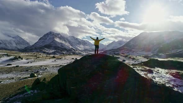Thumbnail for Mountaineer reaches the top of a snowy mountain in a sunny winter day.